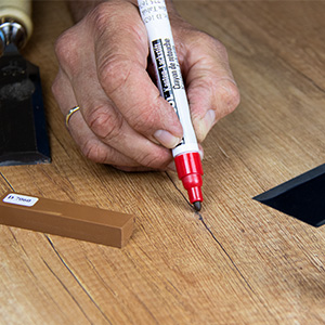 How do you fix deeper scratches in coated chipboard panels?